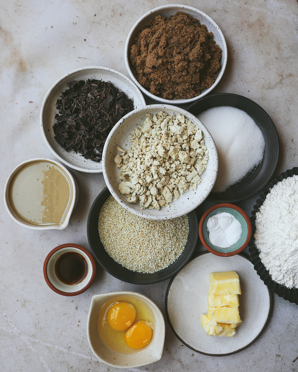 Grouping of ingredients for cookies: from top moving clockwise - brown sugar, granulated sugar, flour, baking soda, baking powder, salt, butter, eggs, sesame seeds, vanilla, halawa/halva, tahini, chocolate chunks